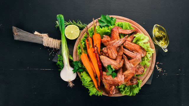 Grilled Chicken Wings with Vegetables and Carrots. On a wooden background. Top view. Copy space.