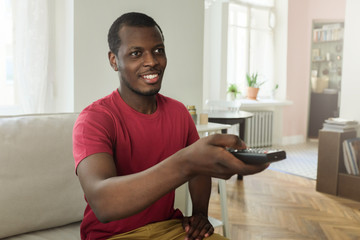 Horizontal photo of African American man sitting on sofa at home watching television, holding remote control in hand, pulling arm forward to switch channels with friendly relaxed smile, having rest