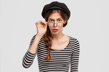 Attentive strict female teacher of French looks scrupulously through eyewear, wears striped sweater and beret, poses against white background. People, emotions and facial expressions concept