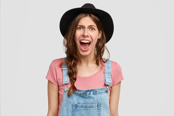 Irritated furious female shouts with anger, being discontent with results of work in her garden, expresses negative emotions, wears countryside casual clothes, stands against white background
