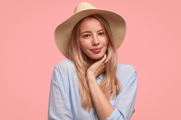 Portrait of attractive lovely young female wears elegant hat and shirt, holds hand under chin, shows her natural beauty, stands against pink background. People, feminity and fashion concept.