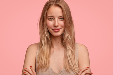 Cropped shot of beautiful blonde young female with straight hair, has pleased expression, keeps arms folded, smiles gently, satisfied as has date with stranger, isolated over pink background