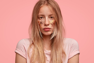 Headshot of beautiful woman with glitter on face and hair, has professional make up, looks seriously, contemplates about something, takes care of appearance, stands over pink background. Monochrome