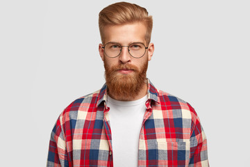 Studio shot of ginger male hipster in eyewear and checkered shirt, looks serious with confident facial expression, recieves necessary information, isolated over white background. People and style