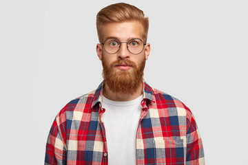 Portrait of handsome young successful male designer with thick ginger beard, looks surprisingly at camera, has serious expression, wears big round spectacles and checkered shirt, stands indoor