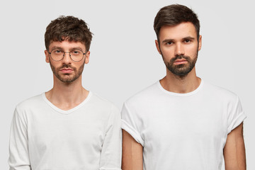Indoor shot of serious two Caucasian men look directly at camera, wear casual clothes, have stubbles, work as friendly team, stand against white background. People, facial expressions concept