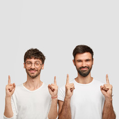 Positive young guys with dark bristle, wear casual white clothes, points with two index fingers upwards, have satisfied expressions, show something above heads, isolated over blank studio wall