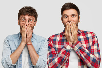 Wall Mural - Joyful guys look with happiness, cover mouthes, have glad expressions, try stop laughing, see something amazing, doesn`t expect recieve unexpected present from friend. Peope, emotions concept