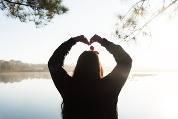 Silhouette of Woman's hands forming a heart shape on morning sunrise.