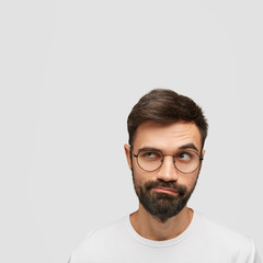 Portrait of attractive unshaven male looks with puzzlement aside, being deep in thoughts, raises eyebrows and purses lips, stands against white background with copy space aside for your promotion