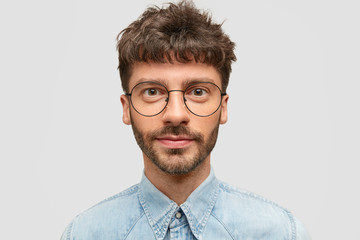 Isolated shot of serious confident unshaven male student in eyewear and denim fashionable shirt, listens information about exam with attention, tries to remember everything, has appealing look