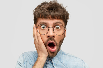 Omg, what I did! Surprised frightened young male with stubble touches cheek and opens mouth, being shocked from seeing how much he should pay in shop, stares through glasses, poses against white wall