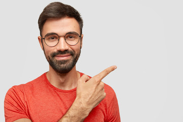 Photo of pleased unshaven European male with cheerful expression, has thick stubble, points aside, shows blank space for your advertising content, stands against white wall, dressed in red outfit
