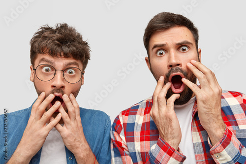 two amazed bearded young guys stare at camera with frightened