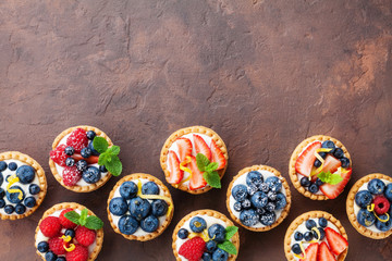 Wall Murals Dessert Delicious berry tartlets or cake with cream cheese decorated lemon peel and mint leaf from above. Tasty pastry desserts.
