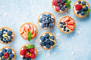 Healthy summer pastry dessert. Berry tartlets or cake with cream cheese top view.