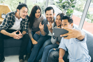 GROUP OF MULTI NATION FRIENDS TAKE SELFIE TOGETHER WITH HAPPINESS AND JOYFUL