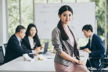 smart and attractive asian designer woman look and smile to camera in meeting room office background