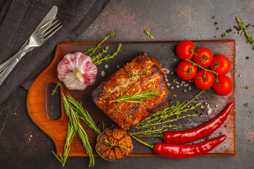 Whole piece of roast pork  with thyme, rosemary, garlic on a wooden board, dark background, top view, copy space.