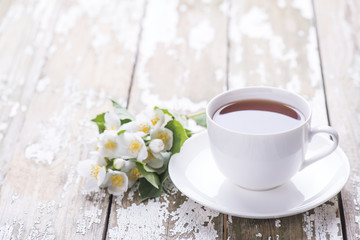 Green tea in the white cup with flowers of jasmine on a wooden old background.