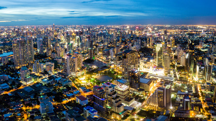 Wall Mural - Aerial view of Bangkok skyline and skyscraper on Sukhumvit center of business in capital. Panorama of modern city and BTS skytrain with Benjasiri park on Asoke junction in Bangkok Thailand at night