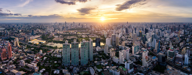 Wall Mural - Aerial view of Bangkok skyline and skyscraper on Sukhumvit center of business in capital. Panorama of modern city and BTS skytrain with Benjakiti park on Asoke junction at Bangkok Thailand on sunset