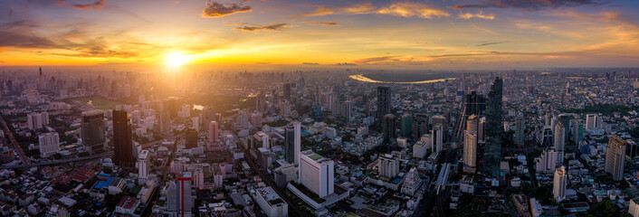 Wall Mural - Aerial view of Bangkok skyline panorama and skyscraper with light trails on Silom road center of business in capital. Modern city and BTS skytrain with Chao Phraya river at Bangkok Thailand on sunrise
