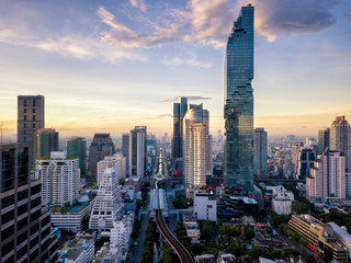 Wall Mural - Aerial view of Bangkok skyline and skyscraper on Silom road center of business in capital. Modern city and BTS skytrain with Chao Phraya river at Bangkok Thailand on sunrise