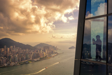 Fototapete - Young man traveler take a photo of Hong Kong City skyline at sunset  from sky 100 Hongkong.