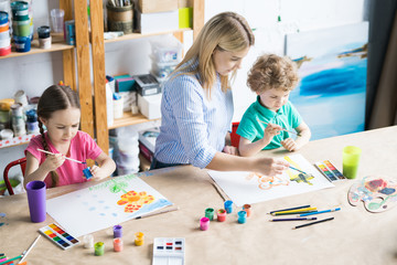 High angle portrait of young woman drawing with two children sitting at wooden table in modern art studio for kids