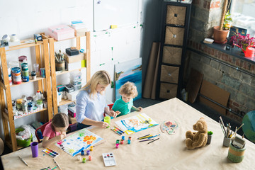 High angle portrait of young woman drawing with two children sitting at wooden table in modern art studio for kids, copy space