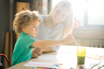 Warm toned side view portrait of cute little boy paining pictures in sunlight sitting at table  with young mother or teacher, copy space
