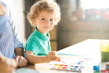 Warm toned portrait of cute little boy looking at camera while painting pictures sitting at table with mom in bright sunlight, copy space