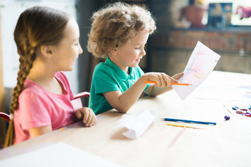 Warm toned portrait of two cute little kids drawing together while sitting at table in art and craft lesson of development school, copy space