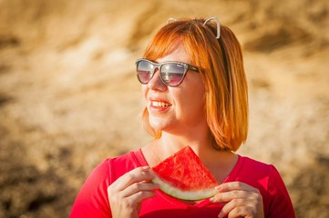 Beautiful Caucasian girl with funny ears eating watermelon with enjoyment. Summer vacation fun stock image. Happiness, weekend picnic.