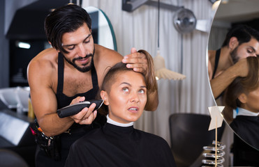 hairdresser with hair clipper with woman