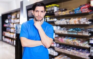 man standing near shelves with sport nutrition