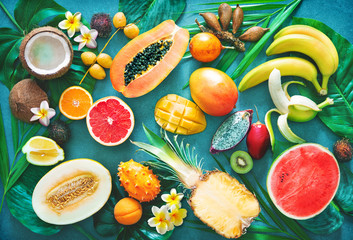 Foto auf Acrylglas Fruchte Assortment of tropical fruits with palm leaves and exotic flowers