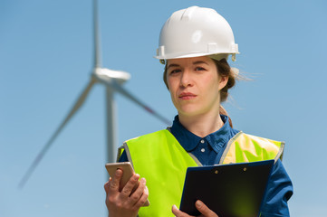 Portrait of a beautiful positive woman architect in a green vest shirt with a smartphone in hand against the backdrop of a windmill