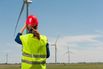 Concept of alternative energy. Rear view woman engineer in green vest and helmet looking towards windmills against the blue sky