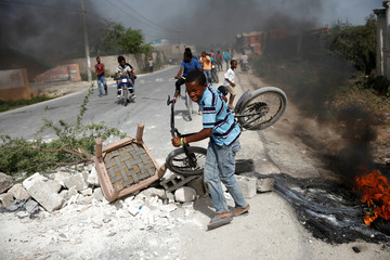 A boy carrying his bicycle passes through a barricade on the outskirts of Croix-des-Bouquets