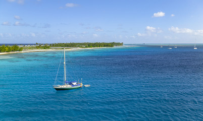 sailing yacht anchoring in the shallow, turquoise lagoon of Fakarava atoll, Tuamotus archipelago, French Polynesia, south pacific