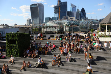 Visitors are overshadowed by office building as they sit in central London