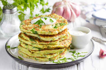 Zucchini pancakes with parsley and sour cream, summer food, tasty snack. High stack in a plate on white wood