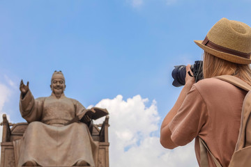 Young Female Traveler Taking Photo of King Sejong Monument at Gwanghwamun Square in Seoul, South Korea
