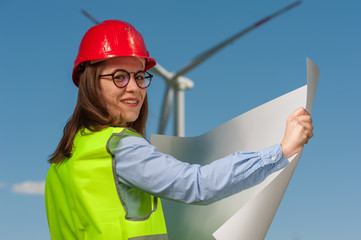 Charming young woman engineer looking at a plan of repair work on the background of a windmill