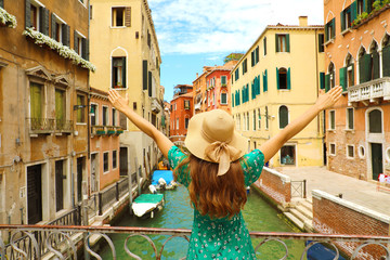 Europe travel vacation fun summer woman with arms up and hat happy in Venice, Italy. Carefree girl tourist in European destination wearing green fashion dress.