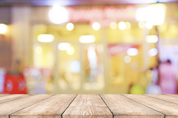 Empty wood table top with blurred light bokeh in night cafe or restaurant background