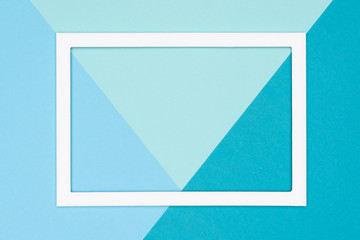 Abstract geometrical flat lay pastel blue and turquoise colored paper background. Minimalism, geometry and symmetry template with empty picture frame mock up.