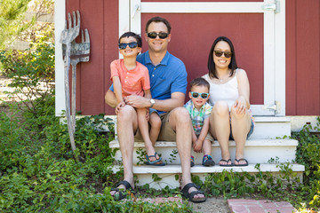 Portrait of Caucasian and Chinese Couple with Their Mixed Race Young Boys Wearing Sunglasses